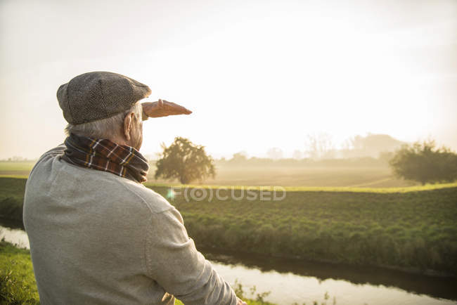 Senior man in rural landscape looking at view — Stock Photo