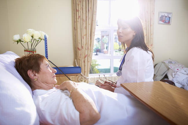 Senior woman lying in hospital bed talking to doctor — Stock Photo