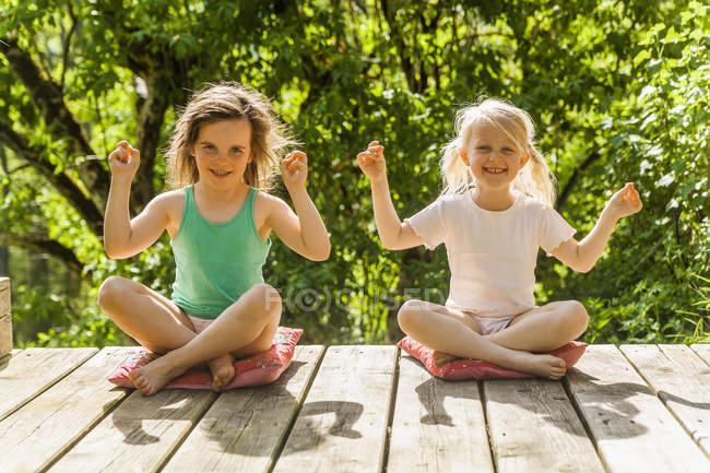 Zwei lächelnde Mädchen auf Holzterrasse — Stockfoto