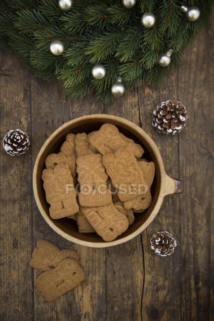 Taza de galletas de almendra, conos de abeto y rama de abeto decorado en madera - foto de stock