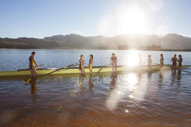 Портрет гребной команды, стоящей возле лодки в воде — стоковое фото