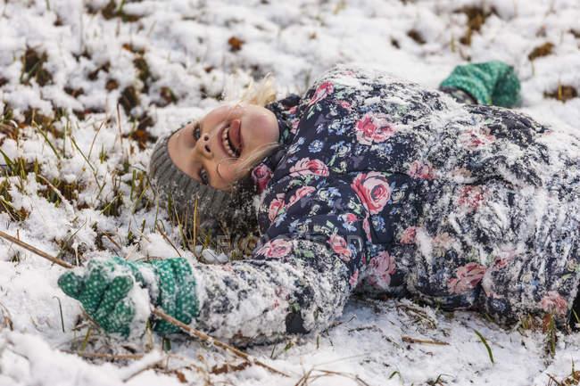 Bambina con la lingua distesa sdraiata sulla neve — Foto stock