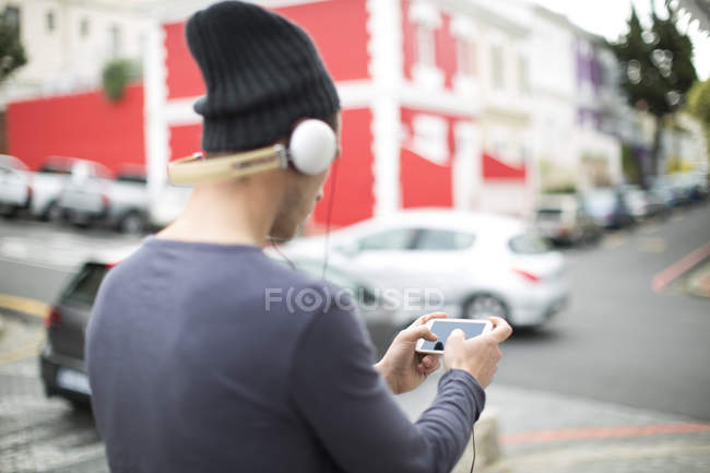 Young man with headphones and smartphone listening music — Stock Photo