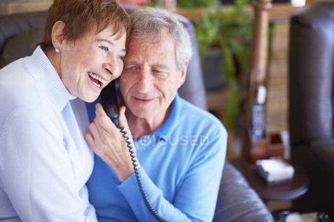 Happy senior couple sharing telephone receiver at home — Stock Photo