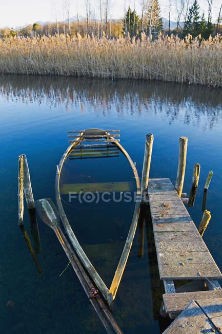 Alemania, Baviera, Baviera superior, lago Staffelsee, hundido bote de remos en el embarcadero - foto de stock