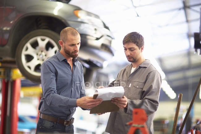 Car mechanic with client in repair garage — Stock Photo
