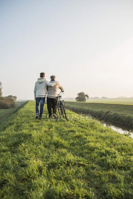 Senior homme et son petit-fils dans le paysage rural avec vélo — Photo de stock