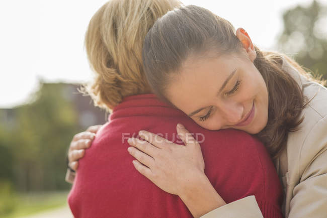 Granddaughter and her grandmother caressing each other — Stock Photo