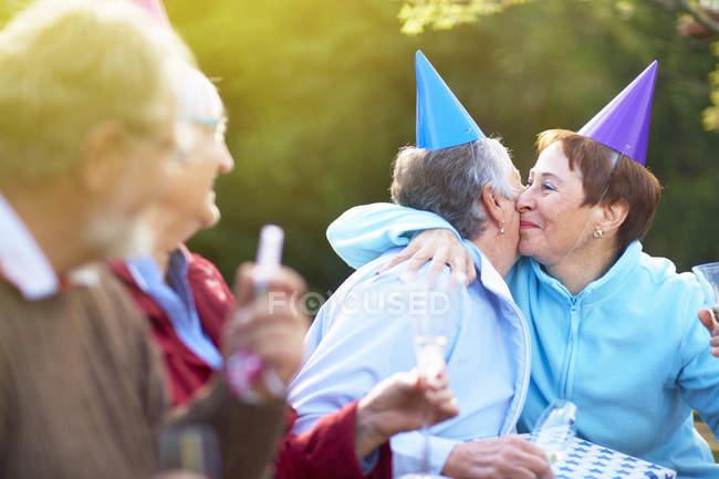 Старший, друзі обіймаються на день народження садові — стокове фото