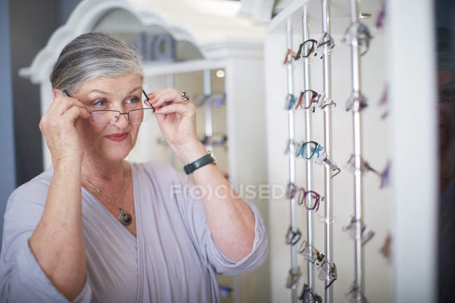 Senior woman at the optician trying on glasses — Stock Photo