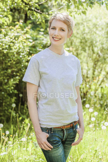 Portrait of smiling woman with short blond hair with hands in pockets — Stock Photo