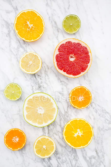 Slices of different citrus fruits on white marble — Stock Photo