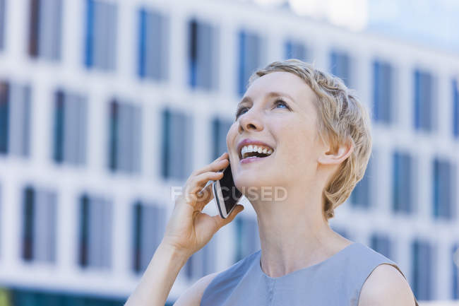 Smiling blond woman telephoning with smartphone — Stock Photo