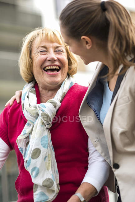 Portrait of laughing senior woman communicating with her granddaughter — Stock Photo