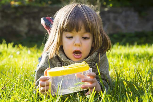 Маленькая девочка лежит на лугу и смотрит на огненного жука. — стоковое фото