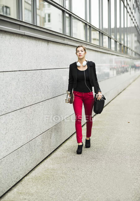 Young woman with skateboard and headphones walking on street — Stock Photo