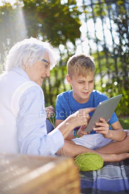 Nieto y abuela con tableta digital en el Parque - foto de stock