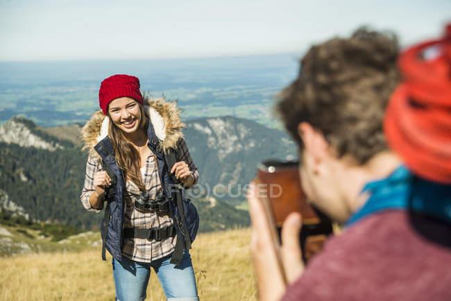 Austria, Tirolo, Tannheimer Tal, giovane uomo che fotografa la fidanzata sul prato alpino — Foto stock