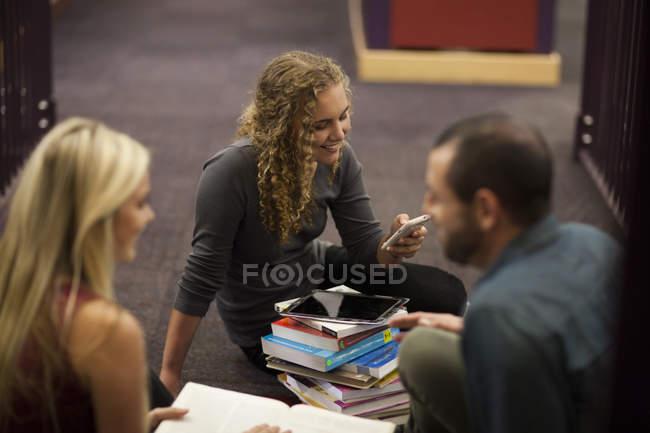 Студенты в библиотеке с книгами, мобильным телефоном и цифровым планшетом — стоковое фото