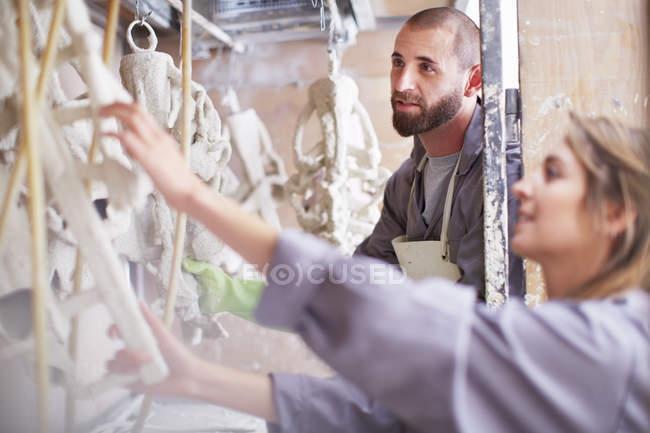 Craftspeople preparing ceramic shell around casting mold — two