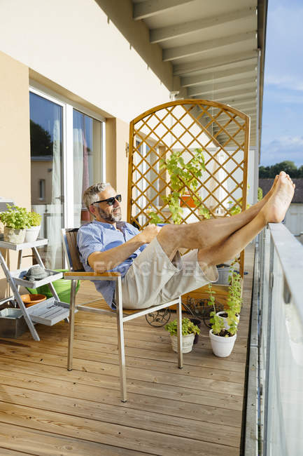 Man wearing sunglasses relaxing on his balcony — Stock Photo