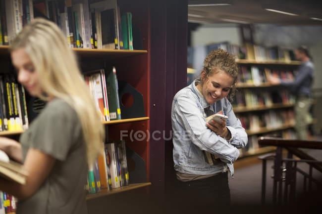 Studentessa in una biblioteca guardando cellulare — Foto stock