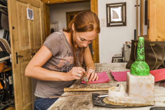 Женщина, производство кожаная сумочка в мастерской — стоковое фото