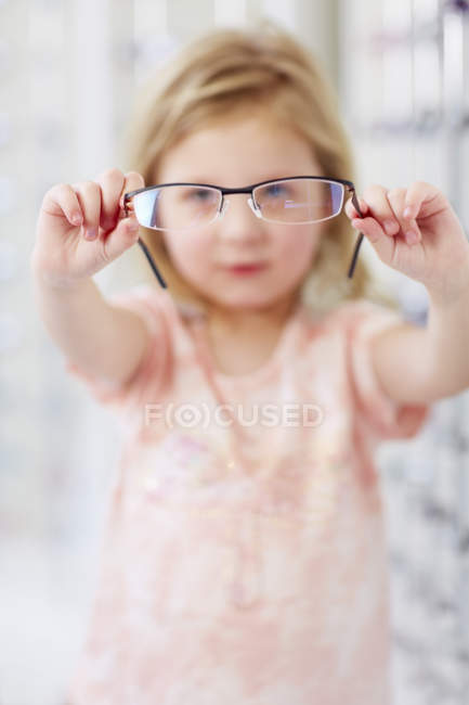 Close-up of Girl holding glasses at optician — Stock Photo