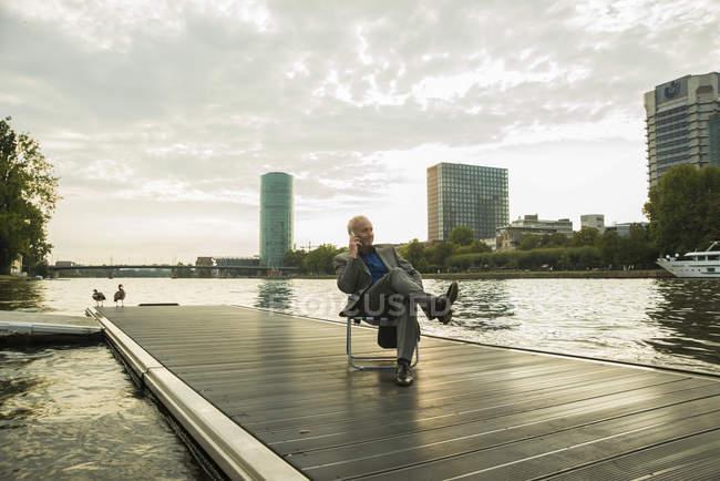 Allemagne, Francfort, homme d'affaires utilisant un téléphone portable à la rivière Main — Photo de stock