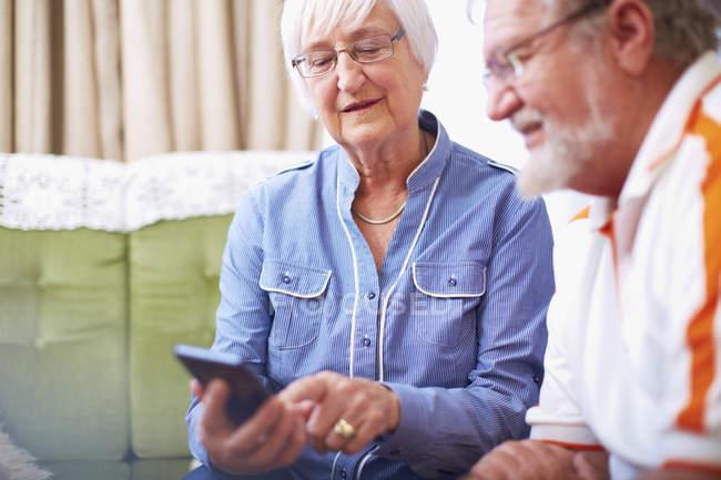 Старшая пара со смартфоном дома — стоковое фото