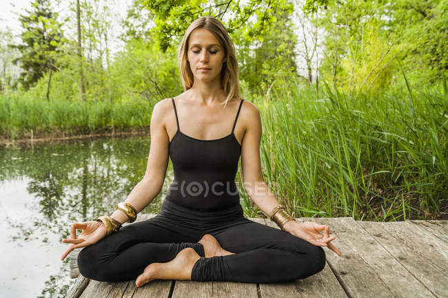 Woman practicing yoga on jetty — Stock Photo