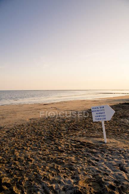 Italy, Gorizia, Grado, view to sandy beach with direction sign at evening twilight — Stock Photo