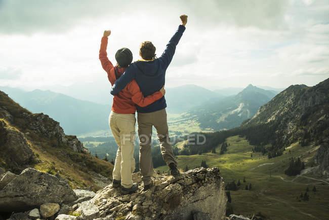 Áustria, Tirol, Tannheimer Tal, jovem casal aplaudindo no topo da montanha — Fotografia de Stock