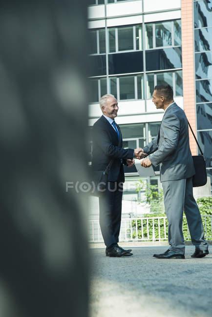 Due uomini d'affari che stringono le mani fuori dall'edificio degli uffici — Foto stock