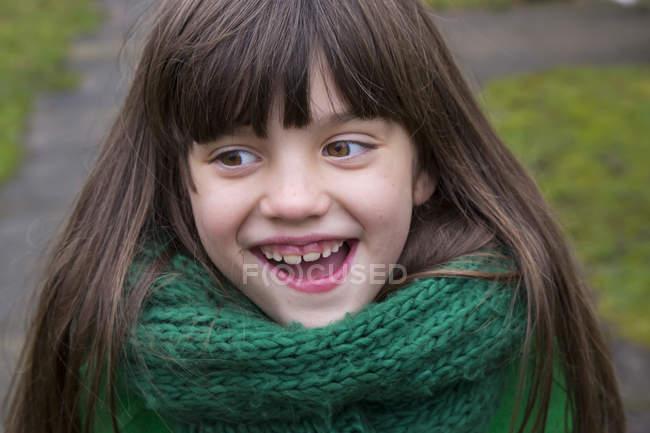 Retrato de niña sonriente con bufanda verde - foto de stock