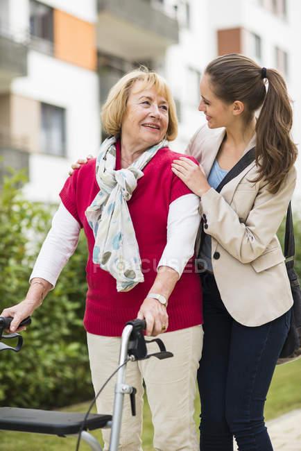 Внучка помогает бабушке с ходунком на колесах. — стоковое фото