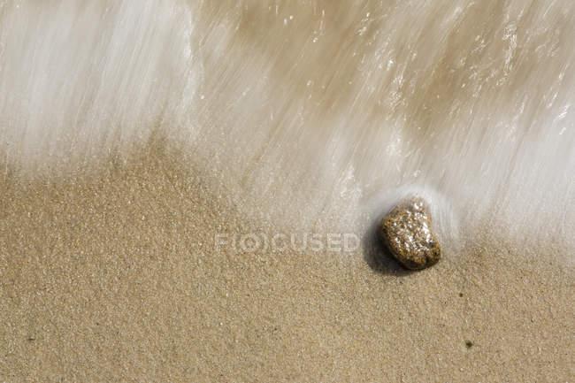 Galets et vagues sur la plage de sable — Photo de stock