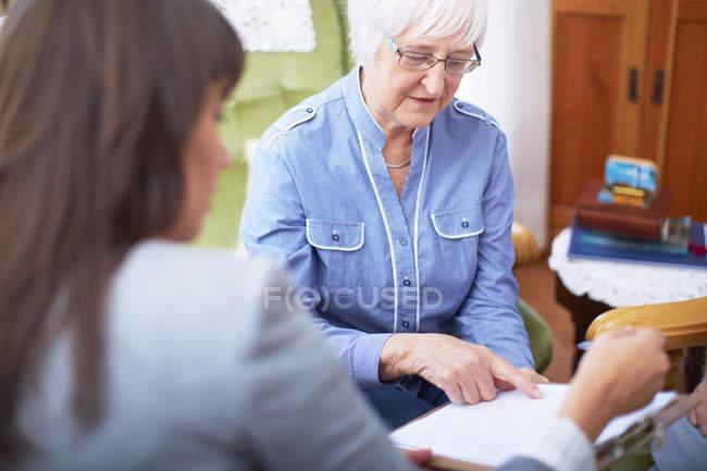 Mujer joven explicando documento a la mujer mayor - foto de stock
