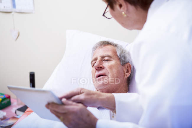 Doctor showing digital tablet to senior man in hospital bed — Stock Photo