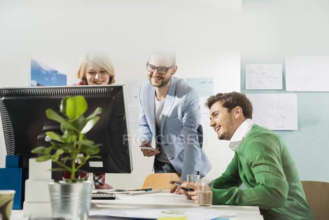 Трое молодых людей в кабинете, глядя на монитор компьютера — стоковое фото