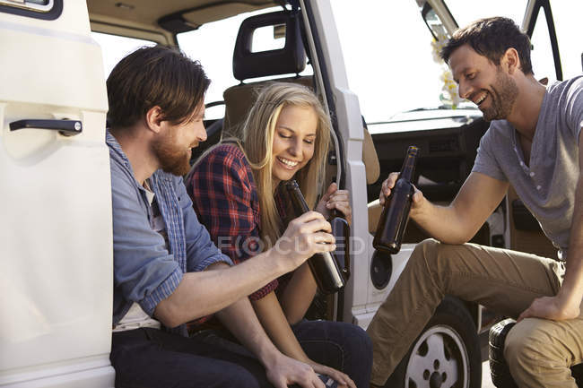 Happy friends celebrating with beer at minivan — Stock Photo