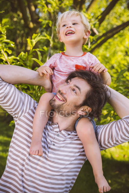 Father carrying son on his shoulders in garden — Stock Photo