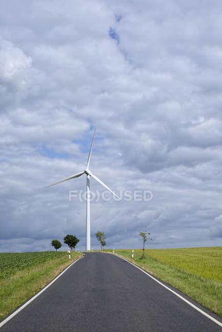 Alemanha, Saxônia, Estrada vazia e turbina eólica pelos campos verdes — Fotografia de Stock