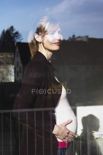 Schwangere schaut aus dem Fenster — Stockfoto