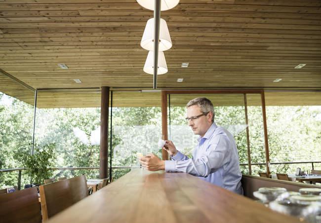 Бизнесмен в кафе, с помощью мобильного телефона — стоковое фото