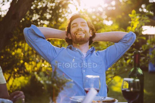 O homem inclinado para trás e sorrindo para jantar na luz da noite — Fotografia de Stock