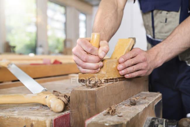 Tischler hobelt Holz in Werkstatt — Stockfoto