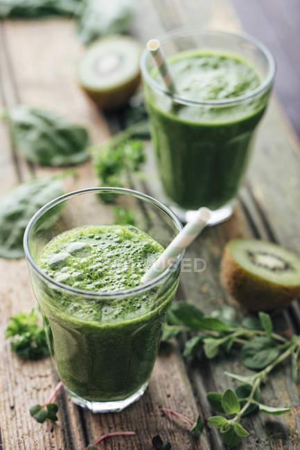 Batido verde de frutas y verduras con espinacas, ensalada, perejil, berros, orégano y kiwi - foto de stock