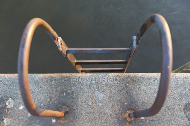 Close-up of old metal ladder on riverside — Stock Photo