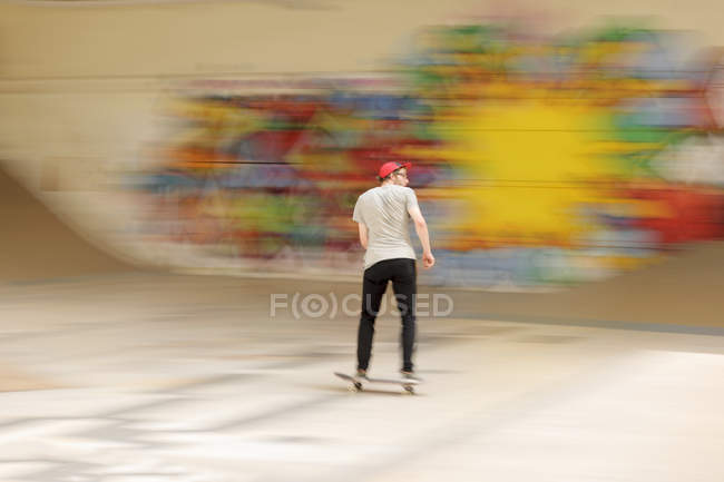 Young man on skateboard in front of colorful blurred graffiti — Stock Photo